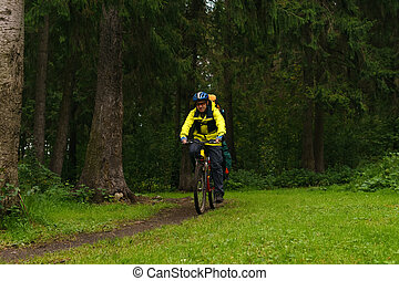 equipped bicycle hiker on a trail in the forest