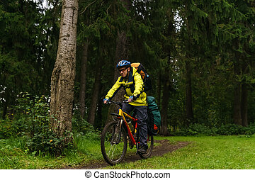 equipped bikepacker on a trail in the forest