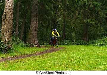 equipped cycling tourist on a trail in the forest