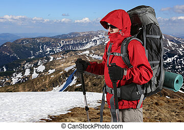 equipped with traveler in a red jacket stands on the hillside