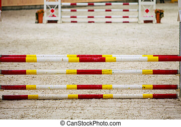 Yellow red white obstacle for jumping horses. Riding competition.