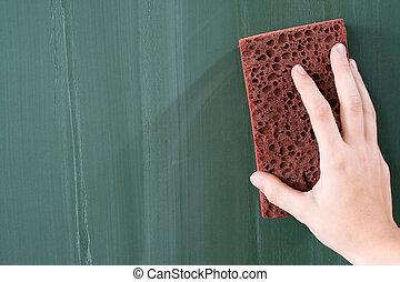 Female hand erasing a greenish blackboard.
