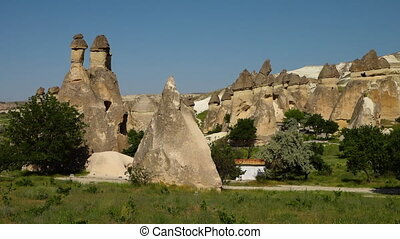 Erect cone-shaped rock formations with a white building -...
