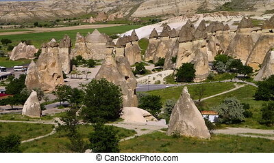 Erect cone-shaped rock formations with vehicles and pathways...