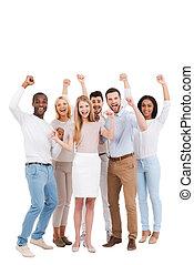 erfolgreich, team., volle länge, von, gruppe, von, glücklich, junge leute, in, klug ungezwungen, tragen, anschauen kamera, und, beibehaltung, arme haben erhoben, während, stehende , gegen, weißer hintergrund