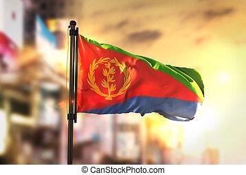 Eritrea Flag Against City Blurred Background At Sunrise Backlight