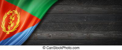 Eritrea flag on black wood wall. Horizontal panoramic banner.