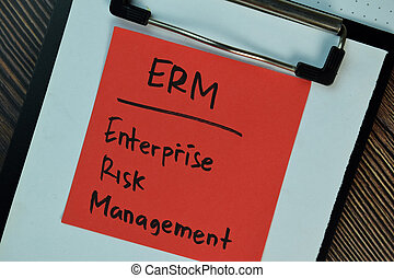ERM - Enterprise Risk Management write on sticky notes isolated on Wooden Table.