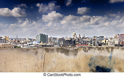 A view of havana skyline under blue sky from eroded wall