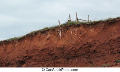 Erosion. - Fence posts falling off small cliff. Erosion on...