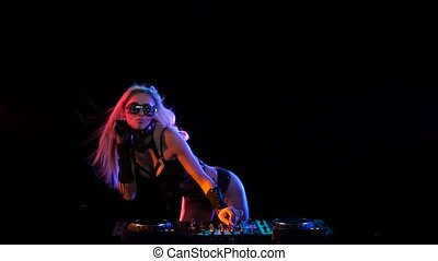 Erotic DJ blonde girl in neon light behind the decks