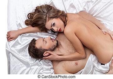 Erotica. Top view of strong man hugs pretty girl