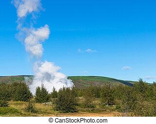 eruption in Haukadalur geyser valley in Iceland - travel to...