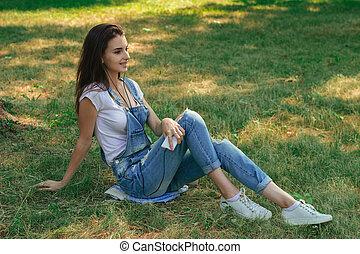 esbelto, morena, adolescente, em, calças brim, overalls, mentir grama, parque