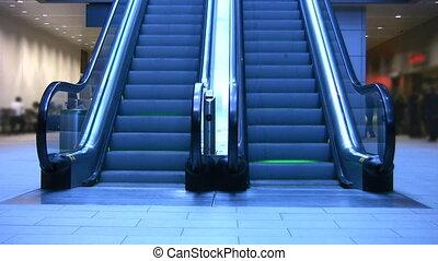 Escalator. - An escalator with neon-green lighting between...