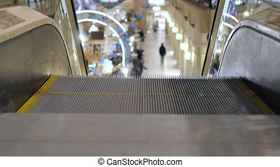 Escalator in the mall close-up. In the background, people are out of focus for shopping.