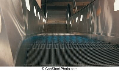 Escalator moves up to the camera. - Escalator moves up to...