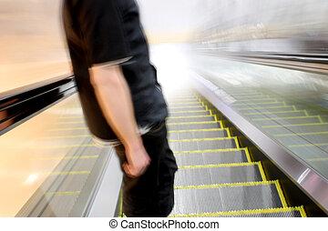 Escalator Toward the Light - Man descending an escalator...