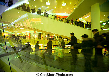 Escalator with buyers in shopping centre through yellow glass protection
