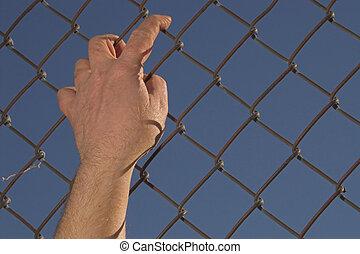 Escape - A person attempting an escape over a chain link ...