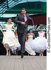 Laughing groom is escaping from the crowd of brides.