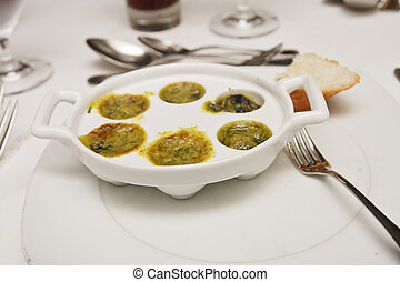 A dish of escargot with butter and garlic sauce