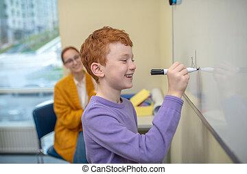 escrita, menino, vermelho-haired, símbolos, whiteboard, sorrindo
