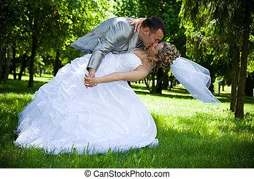 esküvő párosít, csókol, a parkban