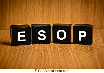 ESOP or employee stock option program word on black block -...