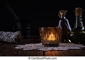 Esoteric still life with burning candle, green vials with drops of alternative medicine and iron mortar on blurred black background and old wooden table top.