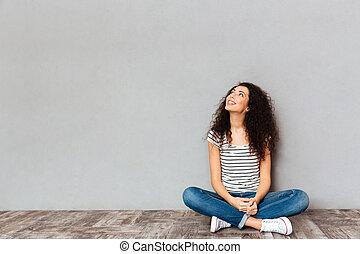 espaço, loto, lado, sobre, pose, cinzento, olhando jovem, parede, posar, chão, femininas, sentando, cópia, roupas casuais
