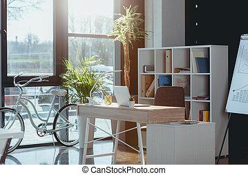 espacio de trabajo, con, computadora de computadora portátil, en, moderno, oficina vacía, bicicleta, posición, en, ventana