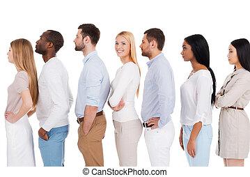 esperar, para, ella, turn., vista lateral, de, hermoso, mujer joven, mirar cámara del juez, y, sonriente, mientras, posición, consecutivo, con, otro, gente, y, contra, fondo blanco