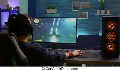 Esport video game r wearing headset and playing online video game for space shooter championship. Online streaming cyber performing gaming tournament using modern technology network wireless