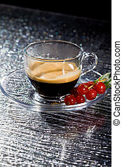Espresso cofee with currants on black glass table