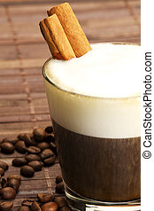 espresso coffee in a short glass with milk froth and cinnamon sticks inside and coffee beans on wooden background