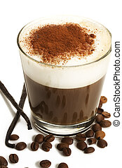 espresso coffee in a short glass with milk froth chocolate powder coffee beans and vanilla beans on white background