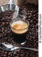 Espresso coffee in glass cup with coffee beans.