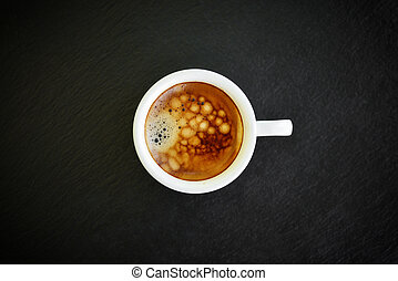 Espresso coffee in small white cup on black slate background...