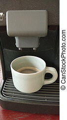 Espresso coffee maker with the cup on a wooden table.