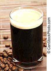 espresso in a glass with coffee beans on wooden background