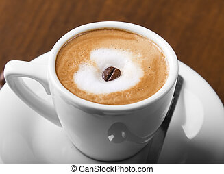 Macchiato coffe with espresso bean in center of steamed milk cream
