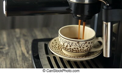 Espresso machine pouring strong looking fresh coffee into a...