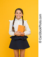 Essay for homework. KId girl student likes to study. Study literature. Private lesson. Adorable child schoolgirl hold copybook. Formal education. School club after classes. Study foreign language