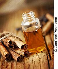 Essence Bottle and Cinnamon Sticks on Wooden Board