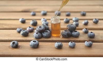 Essence of blueberry on wooden background in beautiful glass...