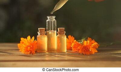 Essence of calendula flowers on table in beautiful glass...