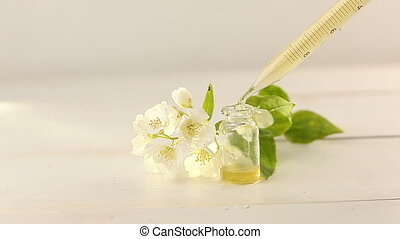 Essence of flowers on white background in beautiful glass jar