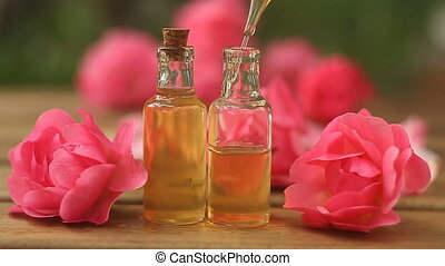 Essence of rose on table in beautiful glass bottle