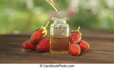 Essence of Wild strawberry on table in beautiful glass jar